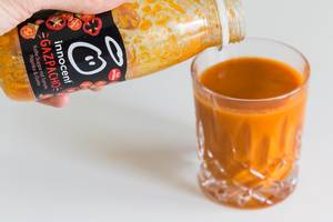"""Hand schüttet die kalte Gemüsesuppe mit dem spanischen Namen """"Gazpacho"""" von Innocent aus der kleinen Flasche in ein Glas vor weißem Hintergrund"""