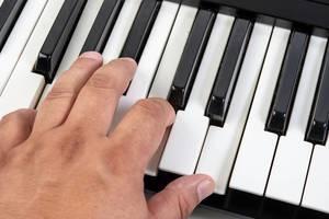 Hand spielt auf weißen und schwarzen Keyboardtasten