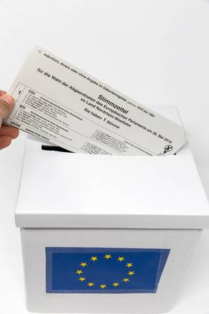 Hand steckt den Europawahl-Stimmzettel für Briefwähler symbolisch in eine Abstimmungsurne