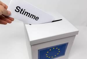 """Hand steckt einen Wahlschein mit der Aufschrift """"Stimme"""" in einen weißen Karton mit Europaflagge als Wahlurne"""