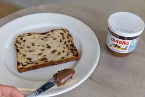 Hand streicht Nutella mit Messer auf Brot mit Früchten und Rosinen