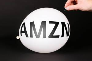 Hand uses a needle to burst a balloon with AMZN text