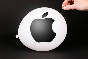Hand uses a needle to burst a balloon with Apple logo