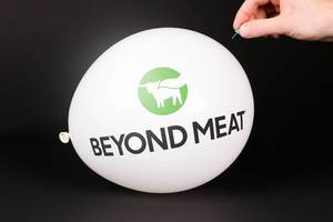 Hand uses a needle to burst a balloon with Beyond Meat logo