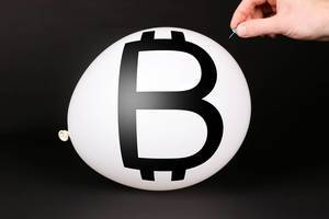 Hand uses a needle to burst a balloon with Bitcoin symbol