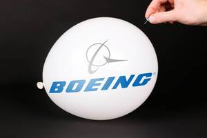 Hand uses a needle to burst a balloon with Boeing logo