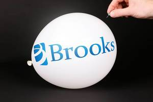 Hand uses a needle to burst a balloon with Brooks logo