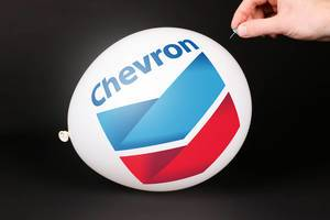 Hand uses a needle to burst a balloon with Chevron Corporation logo