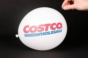 Hand uses a needle to burst a balloon with Costco logo
