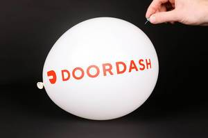 Hand uses a needle to burst a balloon with DoorDash logo