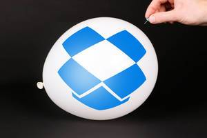 Hand uses a needle to burst a balloon with Dropbox icon