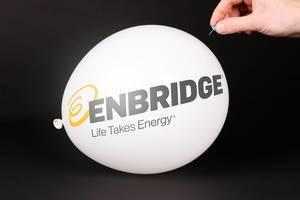 Hand uses a needle to burst a balloon with Enbridge logo