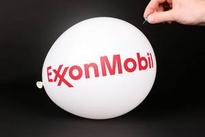 Hand uses a needle to burst a balloon with ExxonMobil logo