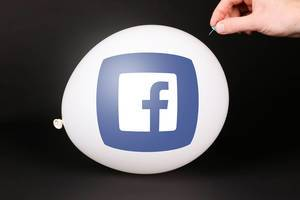 Hand uses a needle to burst a balloon with Facebook icon