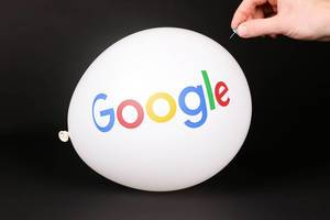 Hand uses a needle to burst a balloon with Google logo