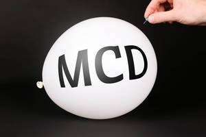 Hand uses a needle to burst a balloon with MCD text