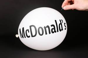 Hand uses a needle to burst a balloon with McDonald