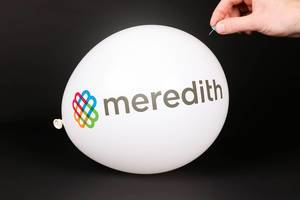 Hand uses a needle to burst a balloon with Meredith Corporation logo