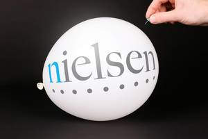 Hand uses a needle to burst a balloon with Nielsen logo