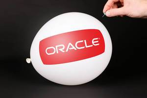 Hand uses a needle to burst a balloon with Oracle logo