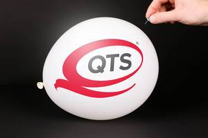 Hand uses a needle to burst a balloon with Quality Technology Services logo