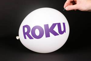 Hand uses a needle to burst a balloon with Roku logo