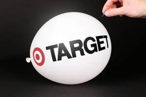 Hand uses a needle to burst a balloon with Target logo