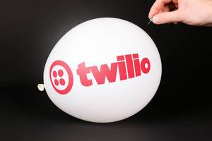 Hand uses a needle to burst a balloon with Twilio logo