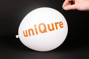 Hand uses a needle to burst a balloon with UniQure logo