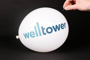 Hand uses a needle to burst a balloon with Welltower logo