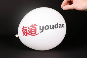 Hand uses a needle to burst a balloon with Youdao logo