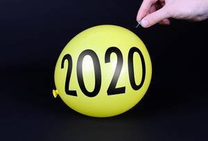Hand uses a needle to burst a yellow balloon with 2020 text