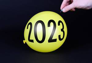 Hand uses a needle to burst a yellow balloon with 2023 text