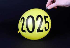 Hand uses a needle to burst a yellow balloon with 2025 text