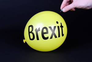 Hand uses a needle to burst a yellow balloon with Brexit text