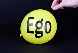 Hand uses a needle to burst a yellow balloon with Ego text