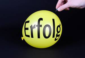 Hand uses a needle to burst a yellow balloon with Erfolg text