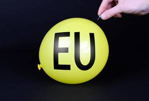 Hand uses a needle to burst a yellow balloon with EU text