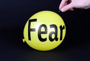 Hand uses a needle to burst a yellow balloon with Fear text