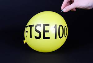 Hand uses a needle to burst a yellow balloon with FTSE 100 text