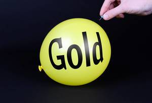 Hand uses a needle to burst a yellow balloon with Gold text