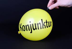 Hand uses a needle to burst a yellow balloon with Konjunktur text
