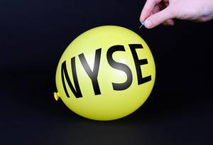 Hand uses a needle to burst a yellow balloon with NYSE text