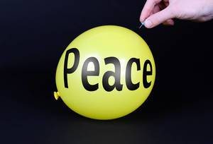 Hand uses a needle to burst a yellow balloon with Peace text