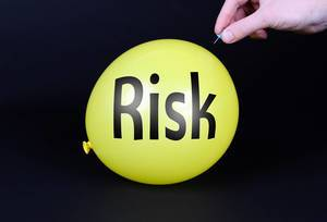 Hand uses a needle to burst a yellow balloon with Risk text