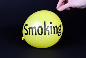 Hand uses a needle to burst a yellow balloon with Smoking text