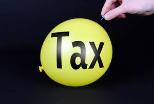 Hand uses a needle to burst a yellow balloon with Tax text