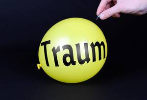Hand uses a needle to burst a yellow balloon with Traum text