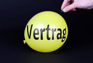 Hand uses a needle to burst a yellow balloon with Vertrag text