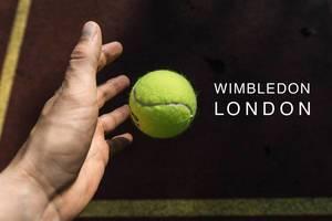 """Hand wirft zum Aufschlag einen Tennisball, neben dem Namen des britischen Tennisturniers """"Wimbledon London"""""""